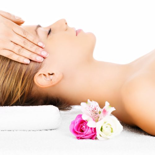 A portrait of a happy woman having a massage over white background